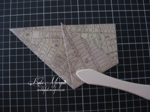 Take one of the lower corners of your triangle and fold it over to the middle of the other triangle side.